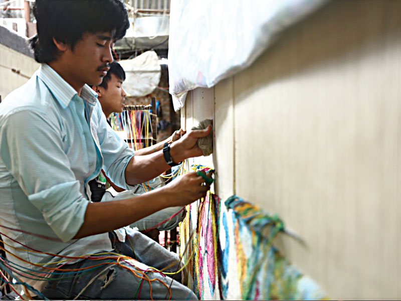 Nepali weavers knotting Creative Matter's Dream Vibrant carpet.